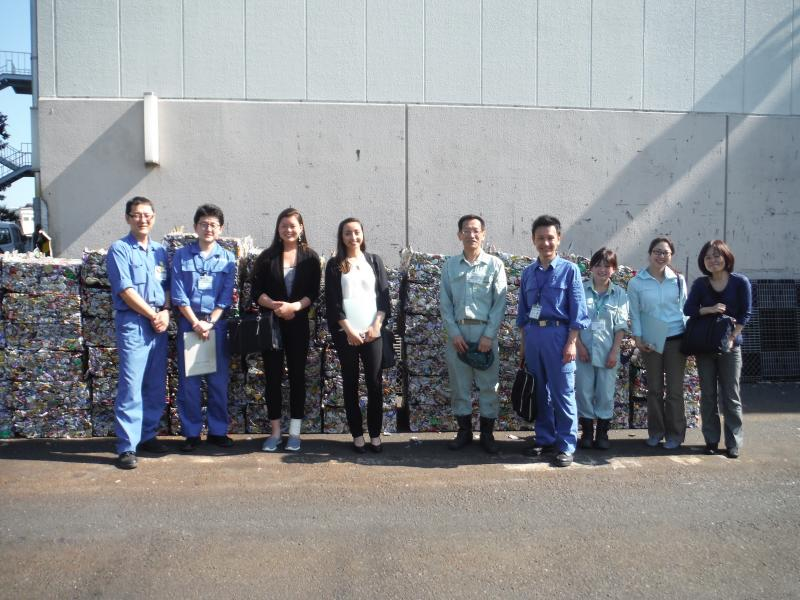 CITYNET Staff pose with Midori recycling facility and Tsuzuki facility staff in front of compressed blocks of plastic